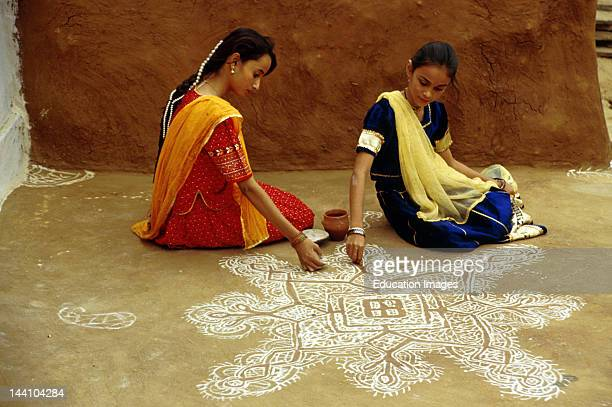 India Young Women Making Chalk Design Known As Rangoli