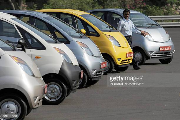 IndiacompanyautoTataNanoSCENE by Phil Hazlewood A Tata Motors employee walks past Nano cars lined up on a test track ahead of a test drive session at...