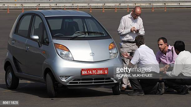 IndiacompanyautoTataNanoSCENE by Phil Hazlewood Foreign journalists take notes as they inspect the Nano car on a track during a test drive session at...