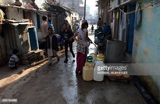 IndiadisasterpollutionBhopalanniversarychildrenFOCUS Indian children walk to school as residents fill up drinking water containers in the JP Nagar...