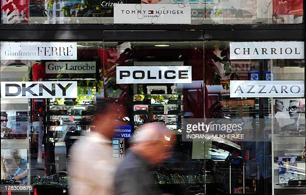 Indiaeconomyconsumersforexeducation by Penelope Macrae Indian pedestrians walk past an optical store selling foreign brands of spectacles in Mumbai...