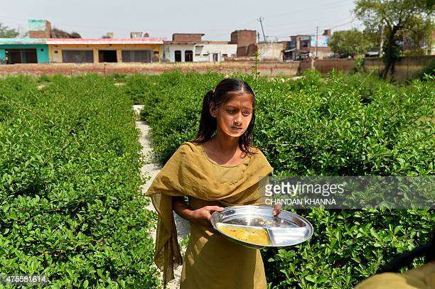 IndiaeducationschoolhealthfoodFEATURE by Abhaya SRIVASTAVA In this photo taken on May 19 an Indian schoolgirl brings her plate to be cleaned after...