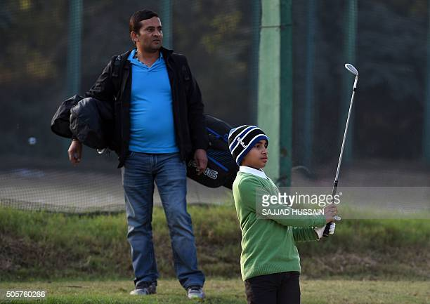 Indiagolfjunior by Abhaya SRIVASTAVA India's No 1 junior golfer and junior world golf championship winner Shubham Jaglan is watched by his father and...
