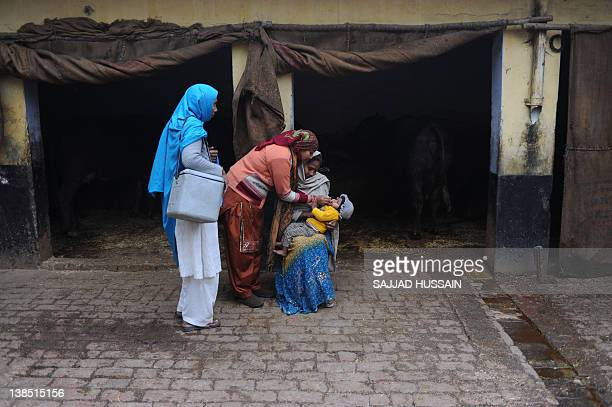 India-health-polio-disease,FEATURE by Ammu Kannampilly This photo taken on January 17, 2012 shows a child being administered polio drops by a health...