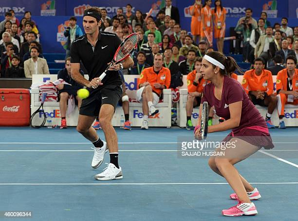 Indian Aces tennis player Sania Mirza and Swiss player Roger Federer return the ball aganist unseen Singapore Slammers players Daniela Hantuchova and...