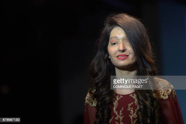Indian acid attack survivor and model Reshma Qureshi presents a creation by designer Archana Kocharat during a fashion show organised by the Make...