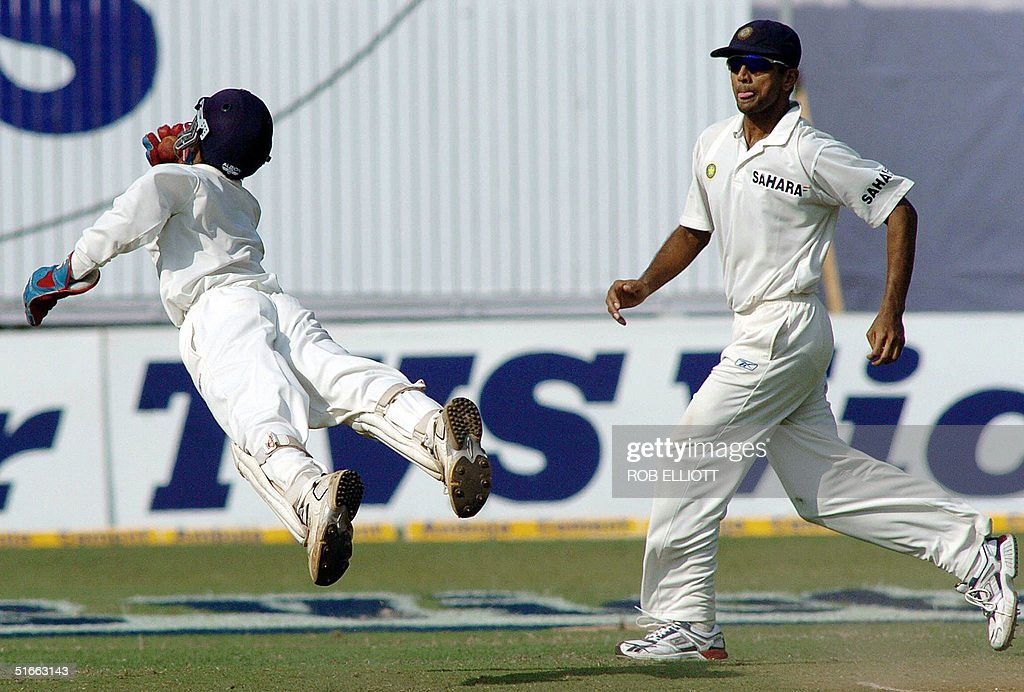 Indian acting skipper, Rahul Dravid (R) runs in as wicket keeper, Dinesh Kartik (L) is in full flight as he takes a catch, not given out by the umpire against Australian batsman, Adam Gilchrist (Unseen) at the Wankhede Stadium, Bombay, 04 November 2004, on day two of the fourth Test between Australia and India. Australia, who shot India out for 104 in the first innings, were 99-3 in reply by tea on the second day of the fourth and final cricket Test . AFP PHOTO/Rob ELLIOTT