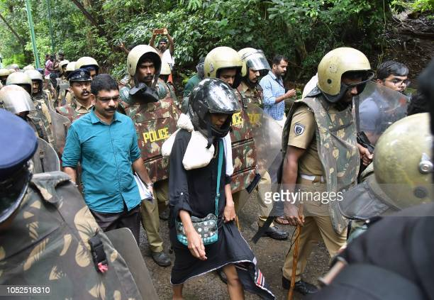 TOPSHOT Indian activist Rehana Fatima walks with police wearing protective gear near the Lord Ayyappa temple complex at Sabarimala in India's...