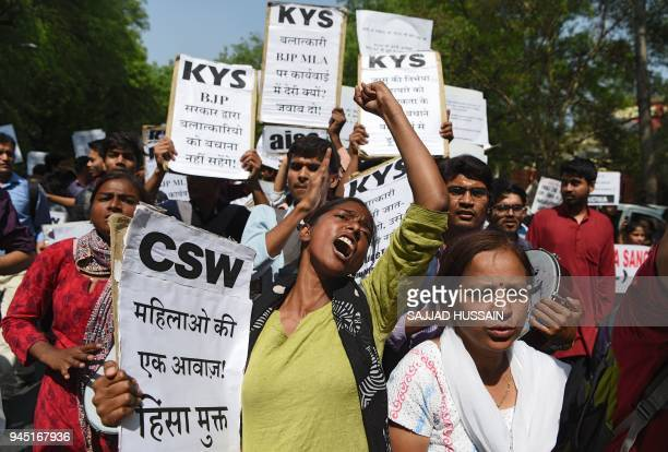 Indian activists and students hold placards and shout slogans during a protest against the alleged political silence over the rape of a child near...