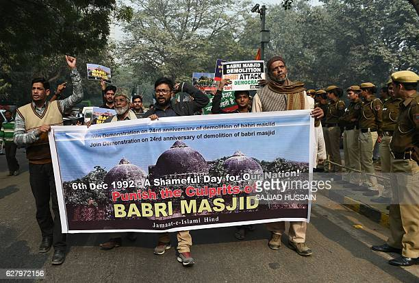 Indian activists carry a banner displaying images of the Babri Mosque as they take part in protest to mark the 24th anniversary of the destruction of...