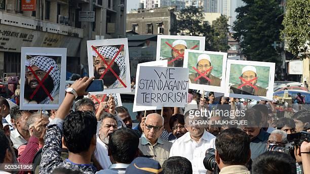 Indian activists carry photographs of the chief of JaisheMohammad Maulana Masood Azhar and chief of Pakistan's outlawed Islamic hardline Jamaat ud...