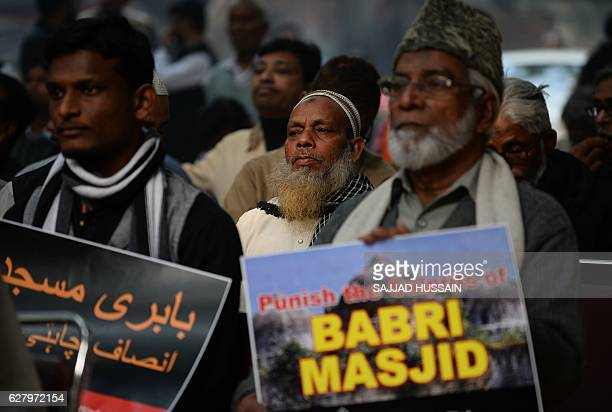 Indian activists carry placards displaying images of the Babri Mosque as they take part in protest to mark the 24th anniversary of the destruction of...
