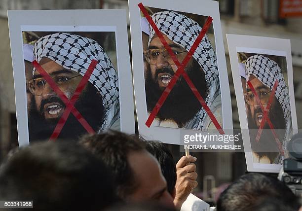 Indian activists carry placards of the chief of JaisheMohammad Maulana Masood Azhar during a protest against the attack on the air force base in...