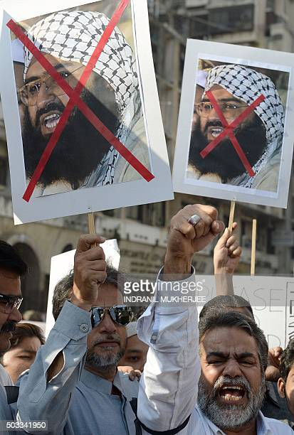 Indian activists carry placards of the chief of JaisheMohammad Maulana Masood Azhar as they shout anti_Pakistan slogans during a protest against the...