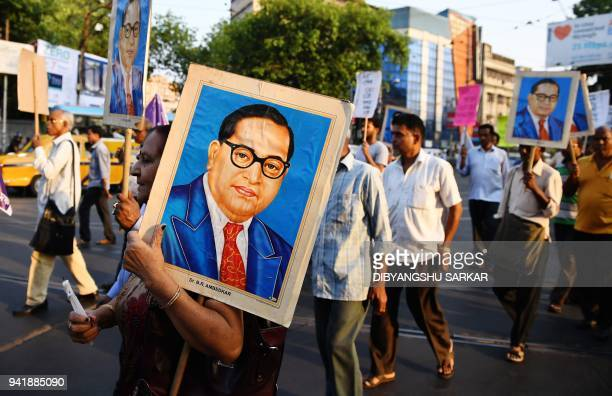 Indian activists carry portraits of 20th century Indian social reformer B R Ambedkar while shouting slogans as they take part in a protest against a...