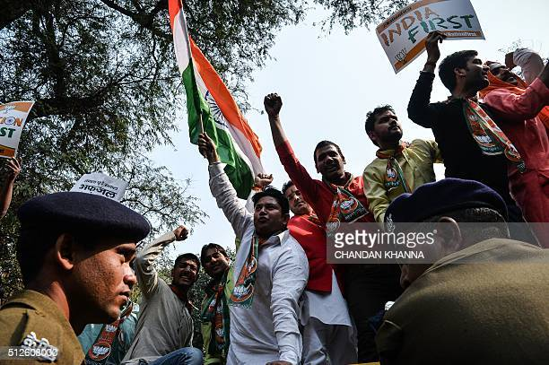 Indian activists from the Bharatiya Janata Yuva Morcha shout slogans and wave flags as they protest against the Congress party leadership demanding a...