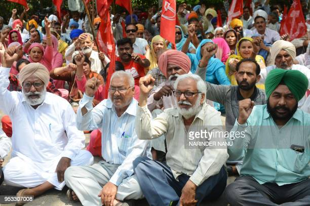 Indian activists from the Communist Party of India along with factory workers shout slogans during a protest against alleged antiworkers policies...