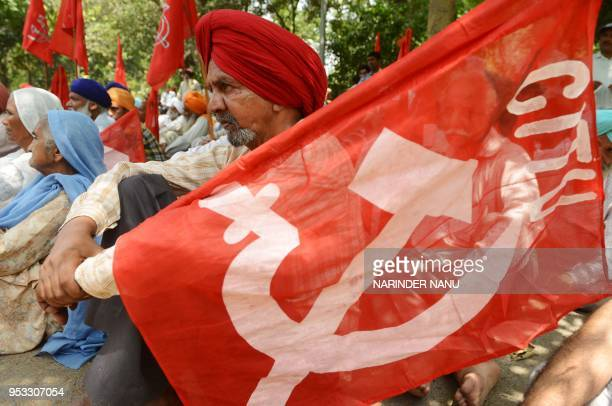 Indian activists from the Communist Party of India along with factory workers listen to a speaker during a protest against alleged antiworkers...