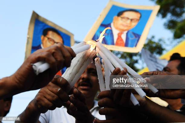 TOPSHOT Indian activists hold candles and portraits of 20th century Indian social reformer B R Ambedkar as they take part in a protest against a...
