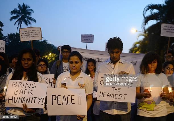 Indian activists hold lighted candles and placards during a vigil in Mumbai on December 22 held for schoolchildren and teachers killed in an attack...