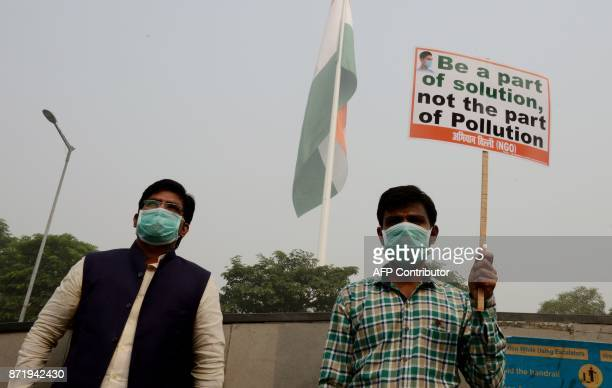Indian activists hold placards and wear facemasks to protect them from pollution during a mask distribution drive at the roadside in New Delhi on...