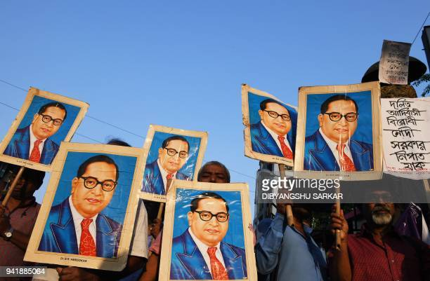 Indian activists holds portraits of 20th century Indian social reformer B R Ambedkar while shouting slogans during a protest against a Supreme Court...