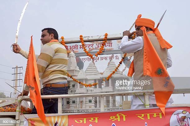 Indian activists of Hindu Bajrang Dal along with Vishva Hindu Parishad organizations hold swords alongside a model of a Ram temple during a...