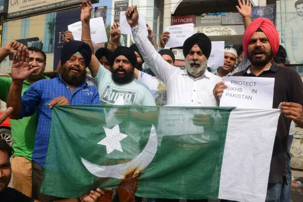 Indian activists of Sikh social workers shout slogans before burning a Pakistani flag during a protest against the eviction of the Pakistan`s first...