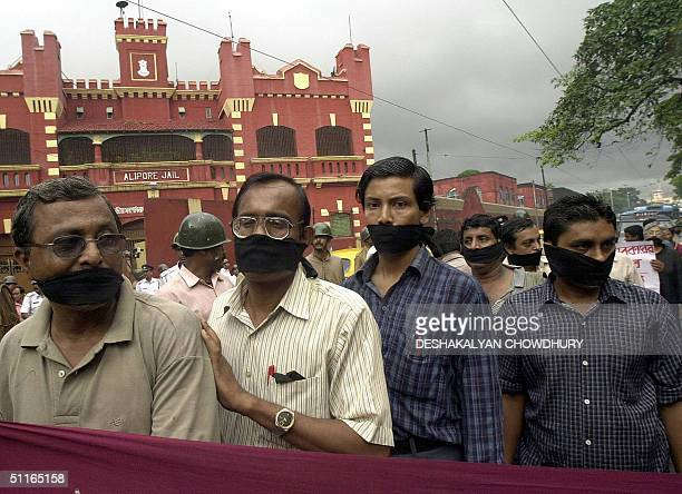 Indian activists of The Association for Protection of Democratic Rights wear black gags and hold banners as they stage a silent protest against the...