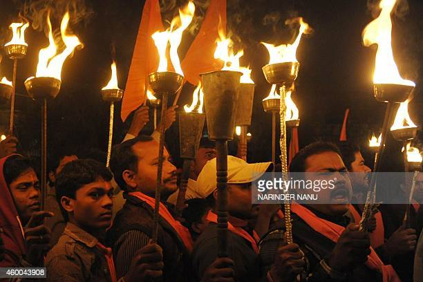 Indian activists of the Hindu Bajrang Dal Party hold torches during a procession marking the 22nd anniversary of the demolition of the Babri Masjid...