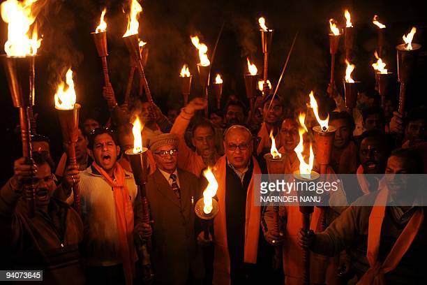 Indian activists of the Hindu Bajrang Dal Party hold torches during a procession held on the 17th anniversary of the demolition of the Babri Masjid...