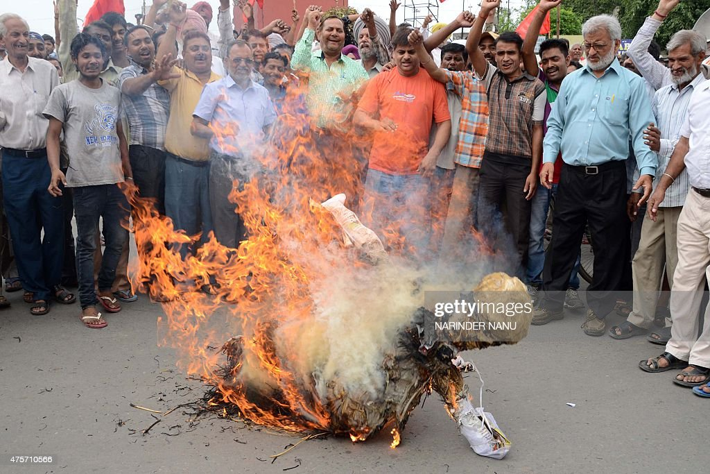 Indian activists of the Textile Ekta Mazdoor Union along with members of the Communist Party of India shout slogans as they burn an effigy of Indian..