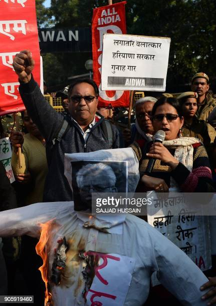 Indian activists shout slogans during a protest as they burn an effigy of the chief minister of Haryana Manohar Lal Khattar in New Delhi on January...