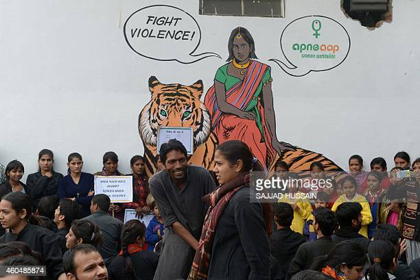 Indian activists take part in a play in front of a mural depicting fictional character Priya who is a rape survivor sitting on a tiger before a march...