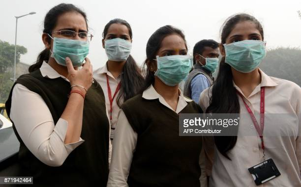 Indian activists wear facemasks to protect them from pollution during a mask distribution drive at the roadside in New Delhi on November 9 2017...