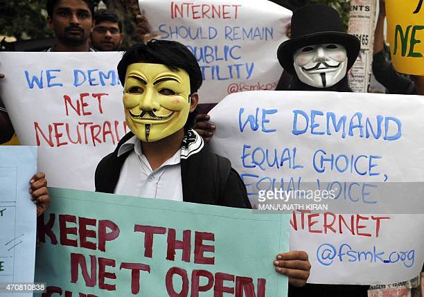 Indian activists wear Guy Fawkes masks as they hold placards during a demonstration supporting 'net neutrality' in Bangalore on April 23 2015 The...