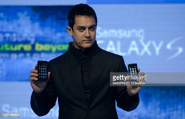 Indian actor Aamir Khan poses for a picture with Samsung smartphones during a product launch in New Delhi on June 16 2010 Samsung launched two new...