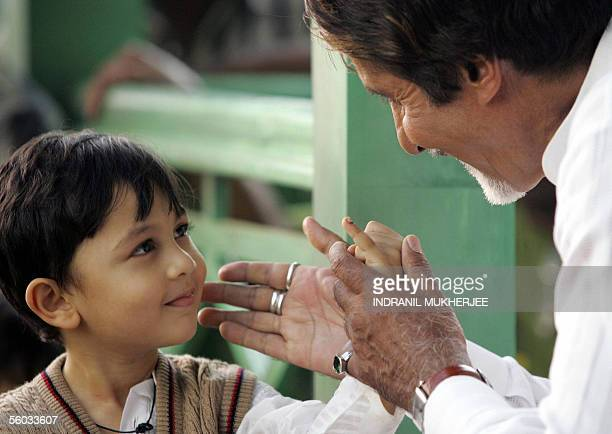 Indian actor Amitabh Bachchan interacts with a child during a polio eradication awareness message shooting in Mumbai 30 October 2005 Bachchan...