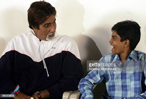 Indian actor Amitabh Bachchan interacts with a child of a HIV positive commercial sex worker as he waits for a AIDS awareness message shooting for...