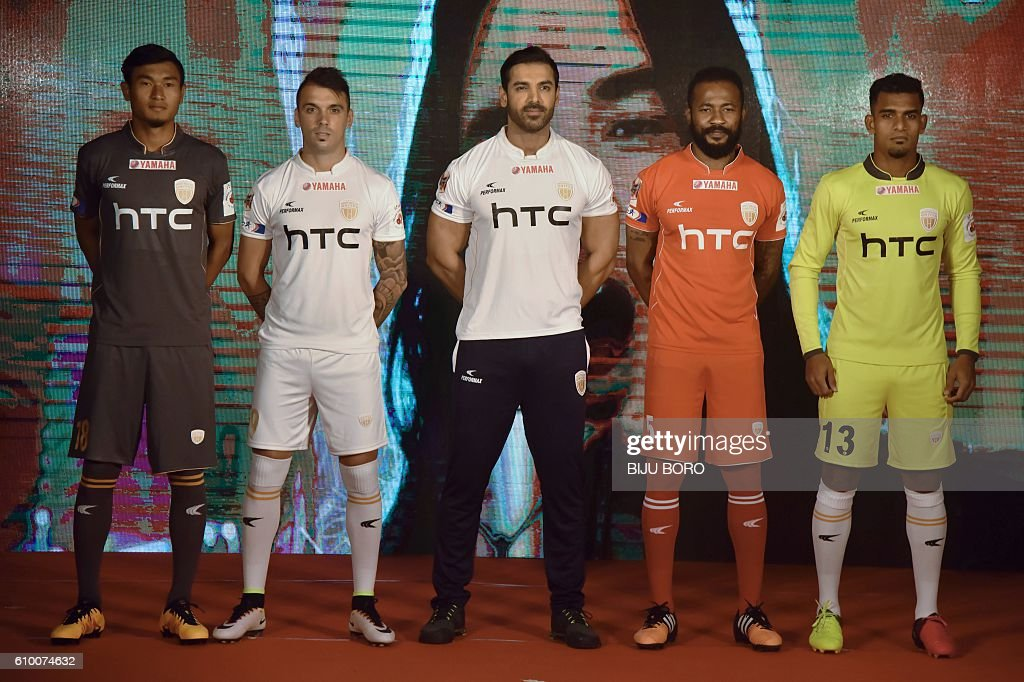 Indian actor and the owner of NorthEast United FC (NEUFC), John Abraham (C) poses with players of NEUFC at the jersey launch in Guwahati on September 24, 2016. The third season of the Indian Super League (ISL) will commence on October 1 with an opening game in Guwahati and runs till December 18, the day of the final. / AFP / Biju BORO