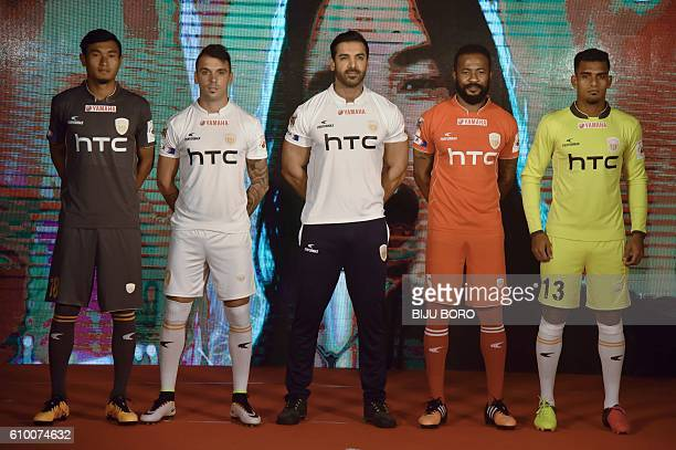 Indian actor and the owner of NorthEast United FC John Abraham poses with players of NEUFC at the jersey launch in Guwahati on September 24 2016 The...