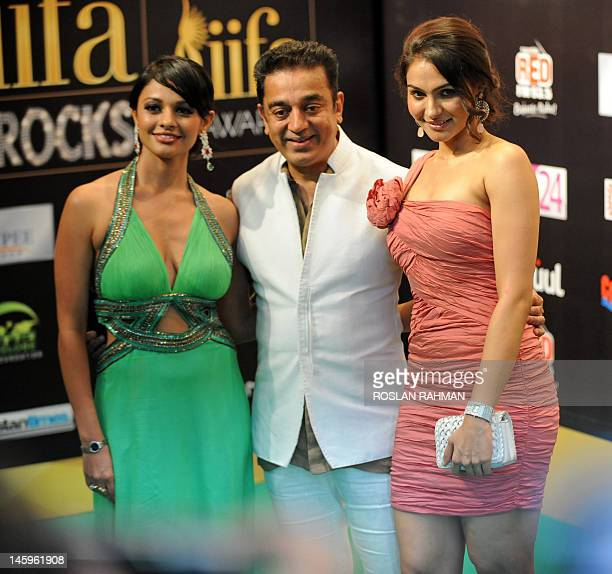 Indian actor Kamal Haasan poses with Bollywood actresses Pooja Kumar and Andrea Jeremiah on the green carpet to attend the International Indian Film...