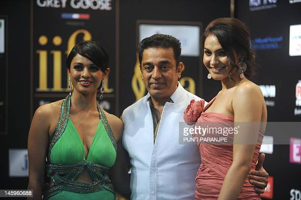 Indian actor Kamal Hasaan poses with costars Pooja Kumar and Andrea Jeremiah on the green carpet for the International Indian Film Academy awards...