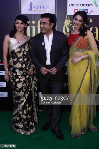 Indian actor Kamal Hassan poses with Bollywood actresses Andrea Jeremiah and Pooja Kumar at the IIFA green carpet event at the 2012 International...