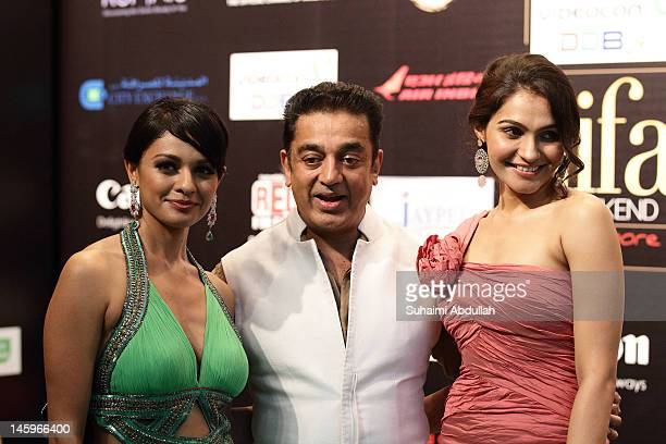 Indian actor Kamal Hassan poses with Bollywood actresses Pooja Kumar and Andrea Jeremiah on the green carpet during the IIFA Rocks Green Carpet on...