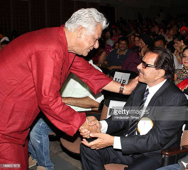Indian actor Om Puri greets Dharmendra at Baisakhi Celebration cohosted by G S Bawa and Punjab Association Of India on April 13 2013 in Mumbai India