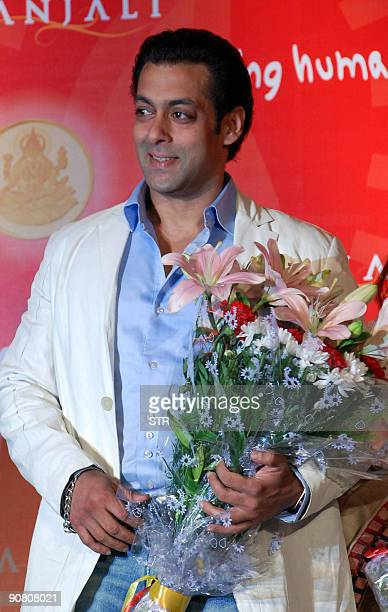 Indian actor Salman Khan poses with a floral bouquet in Mumbai late September 15 at a launch ceremony for his foundation 'Being Human' AFP PHOTO/STR
