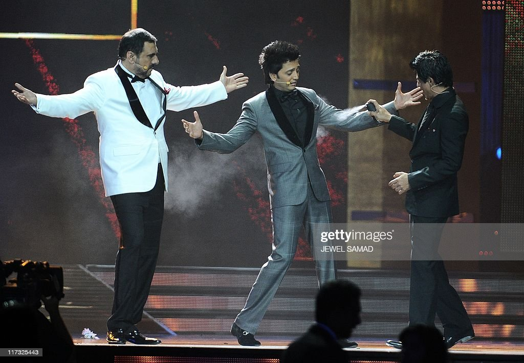Indian actor Shah Rukh Khan jokes with hosts Boman Irani (L) and Ritesh Deshmukh (C) during 2011 International Indian Film Academy (IIFA) awards at the Roger Centre in Toronto, Ontario, on June 25, 2011. AFP PHOTO/Jewel Samad
