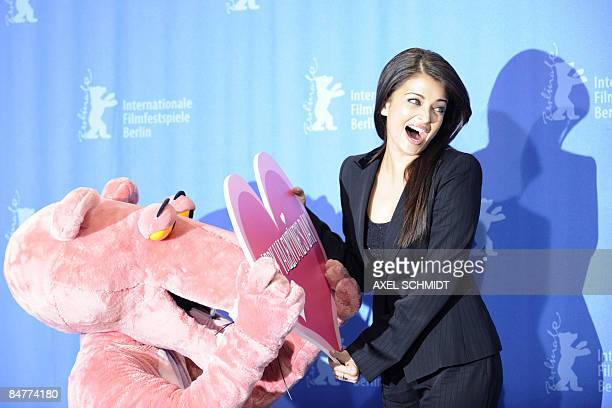 Indian actress Aishwarya Rai Bachchan bursts in laughter as a performer dressed in a Pink Panther costume offers her a Valentine Day's gift during a...
