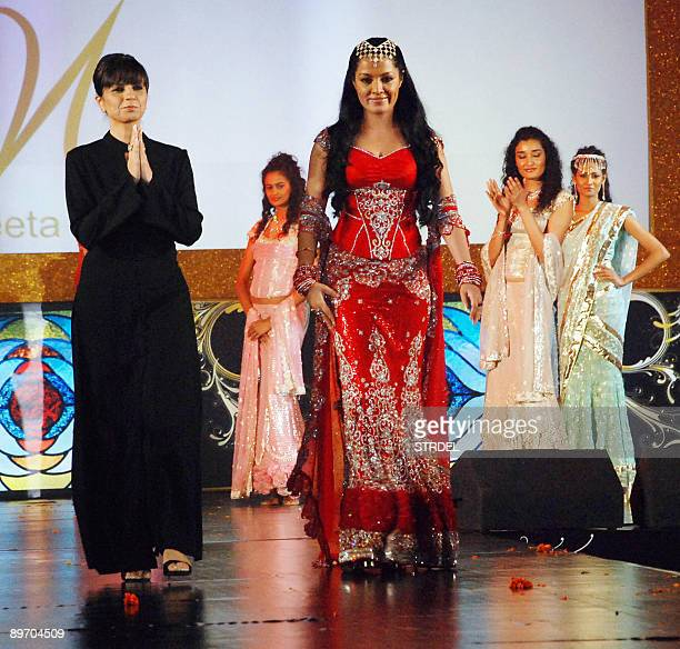 Indian actress and former Miss Universe Celina Jaitley walks with fashion designer Neeta Lulla as she takes part in a fashion show during...
